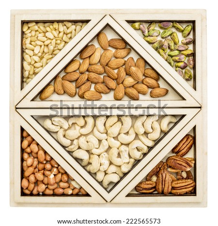 variety of nuts (almond, cashew, pecan, pine, pistachio, peanut) in a geometrical wood tray - stock photo