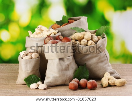 variety of nuts in bags on green background - stock photo