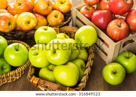 Variety of organic apples in baskets on wood table. - stock photo