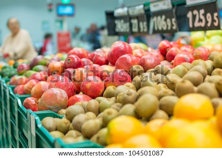 Variety of pomegranate fruits and kiwi fruits in boxes in supermarket - stock photo