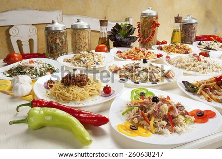 Variety of raw and prepared pasta served on the table. - stock photo