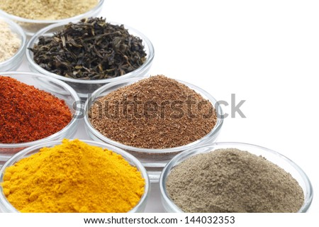 Variety of raw Authentic Indian Spices on square bowl isolated on white background. Focus on Cloves in full-frame. - stock photo
