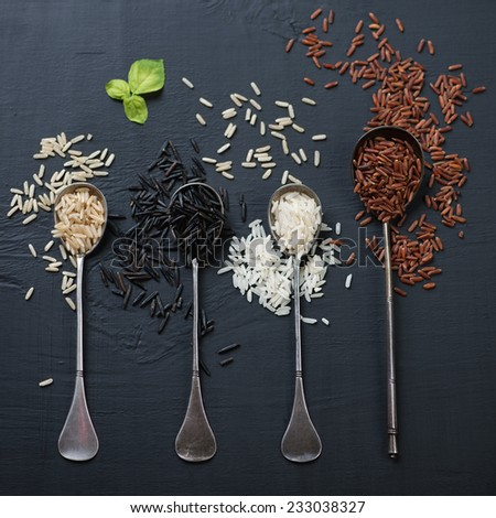 Variety of raw rice in vintage spoons, close-up, view from above - stock photo