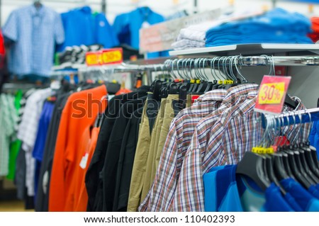 Variety of shirts, t-shirts and trousers on stands in supermarket - stock photo