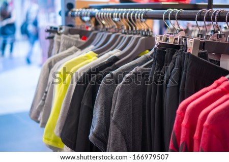 Variety of Sport t-shirts and trousers  on stand in store - stock photo