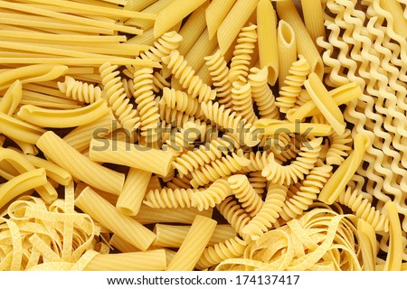 Variety of types and shapes of dry Italian pasta - stock photo