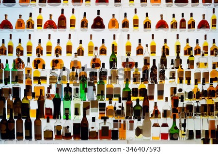 Various alcohol bottles in a bar, back light, all logos removed - stock photo