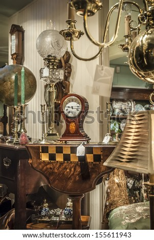 Various antiques for sale viewed through a shop window. - stock photo