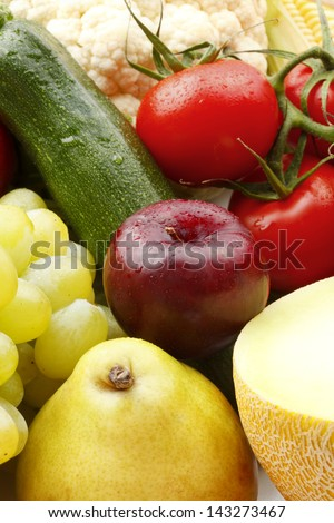 Various, assorted fruits and vegetables( cauliflower, tomato, pear, grape, plum, melon, zucchini, green apple). Vibrant color. - stock photo