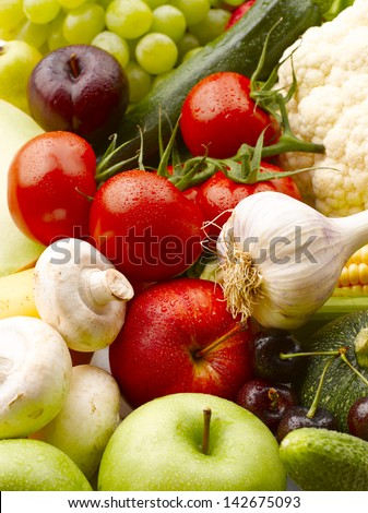 Various, assorted fruits and vegetables(grape, apple, pumpkin, Garlic, mushrooms, cauliflower, corn, maize, tomato, cherry, zucchini, green apple). Vibrant color. - stock photo