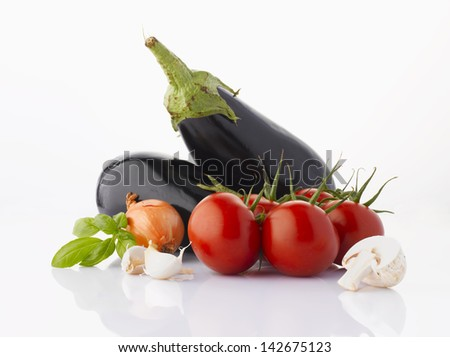 Various, assorted vegetables(eggplant, tomato, garlic, onion, mushrooms, basil leaf) isolated on the white background with soft shadow. Ingredients of italian cuisine. - stock photo