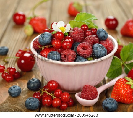 Various berries in a bowl on a brown background - stock photo