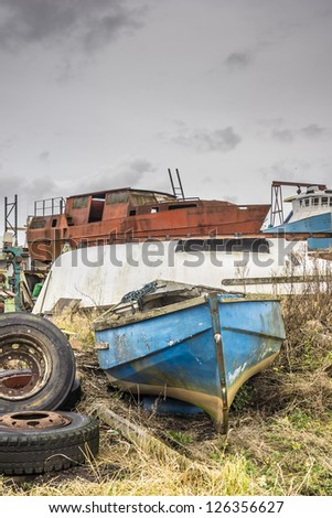 Various boats abandoned,and rotting & rusting away in a yard at Annan harbour - stock photo