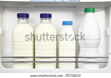 Various bottles of milk in the fridge - stock photo