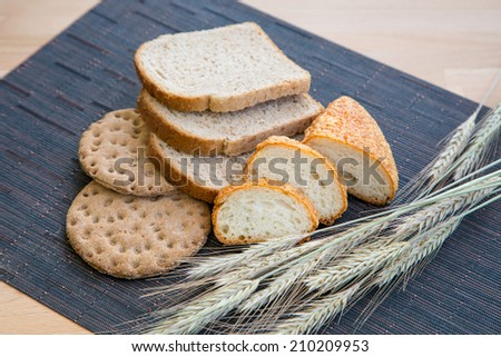 Various bread and wheat on a table - stock photo