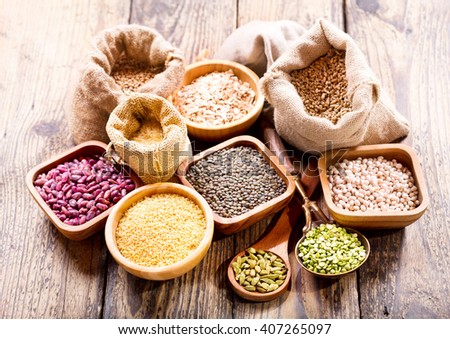various cereals, seeds, beans and grains on wooden table - stock photo