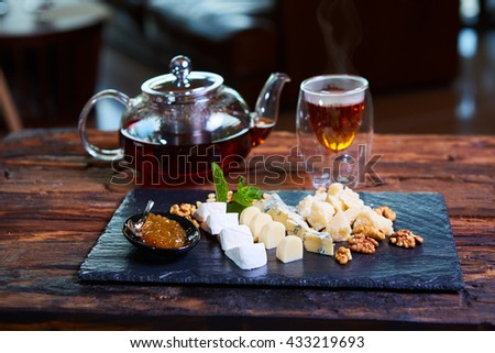 various cheeses and tea on a wooden background - stock photo