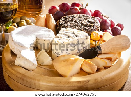 Various cheeses on the board and grapes - stock photo