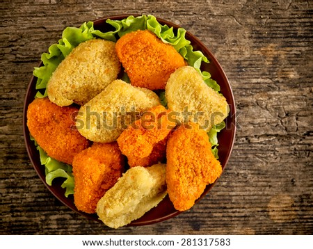 various chicken nuggets on wooden cutting board - stock photo