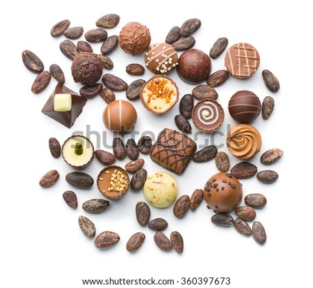 various chocolate pralines and cocoa beans on white background - stock photo