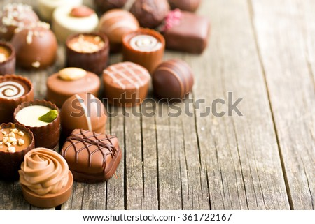 various chocolate pralines on old wooden table - stock photo