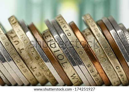 Various coins presented close up on banknote background shown in the distance - stock photo