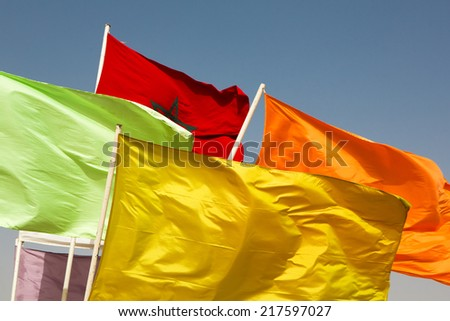 Various colored flags and the flag of Morocco waving against blue sky - stock photo