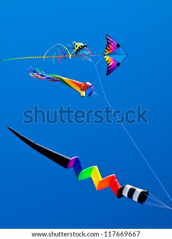 Various Colorful Kites Flying in a Bright Blue Sky - stock photo