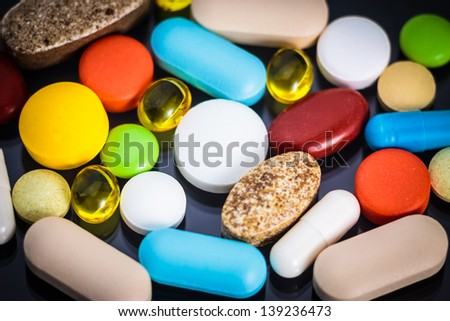 Various colorful pills on black background - stock photo