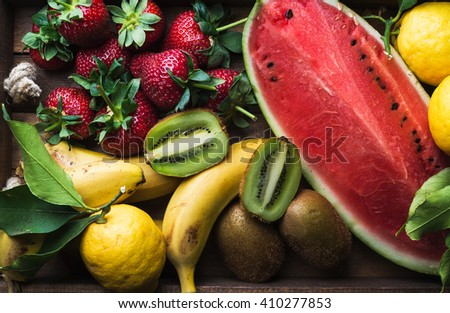 Various colorful tropical fruit selection in wooden tray over dark background, top view. Watermelon, strawberry, lemons and kiwi. Horizontal - stock photo