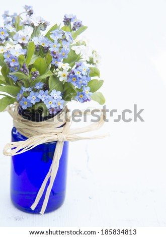 various colors of forget-me-not flowers in a blue vase on a painted white board background - stock photo