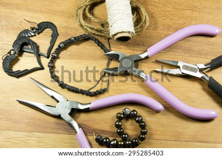 Various craft tools used to make jewelry from wire and beads - stock photo