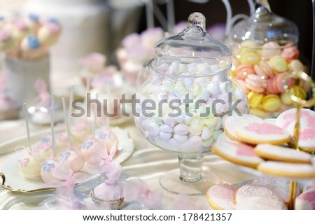 Various decorated colorful candies on a pink table - stock photo