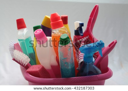 Various detergent bottles in a pink basin - stock photo