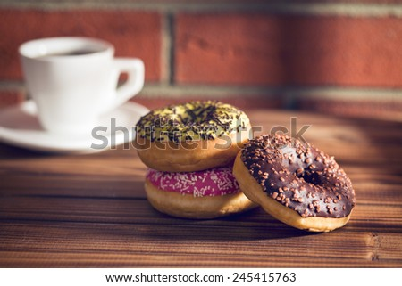 various donuts on wooden table before brick wall - stock photo