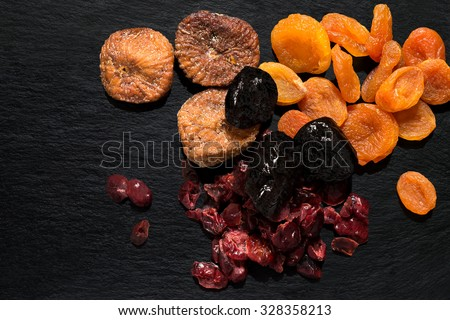 Various dried fruits: apricots, figs, prunes, cranberries on a slate plate - stock photo
