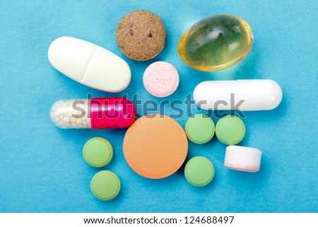 Various drugs, nutrient supplements and vitamins on blue background. - stock photo