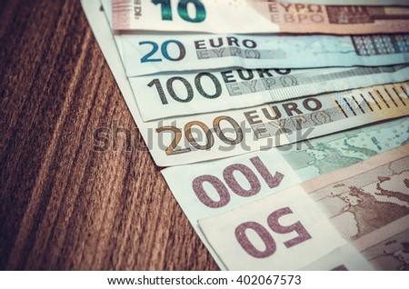 various euro notes on wooden table. toned image - stock photo