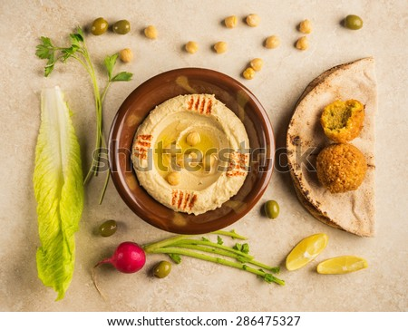 Various food ingredients arranged around bowl of Houmous - a popular Middle Eastern dip. View from top. - stock photo