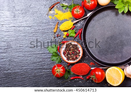 various food ingredients for cooking with empty pan on dark board - stock photo