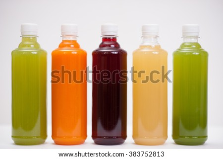 Various fresh vegetable detox juices, colourful smoothies in the bottle on a white background - stock photo