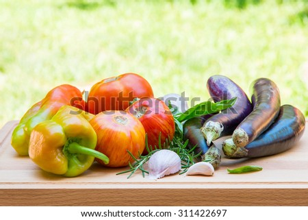 Various fresh vegetables and herbs on wooden cutting board, selective focus. - stock photo
