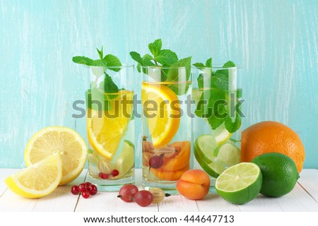 Various fresh vitamin citrus flavored fruit infused water in glasses with fruits on white wooden table against aqua colored wall. - stock photo