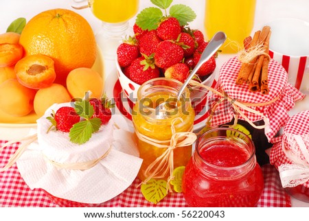 various fruits preserves in jars and fresh fruits on table - stock photo