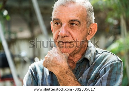 Various gestures of a Cuban senior man while afably conversing with coworkers during a work break in a carpentry shop. - stock photo