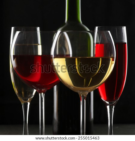 Various glasses of red and white wine with abstract pattern and bottle on black background. - stock photo