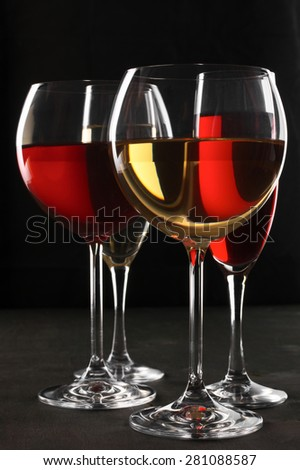 Various glasses of red and white wine with abstract pattern on black wooden background. Shallow DOF, focus on front glass. - stock photo