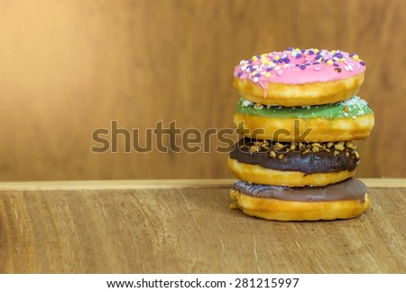 various glazed donuts isolate on wooden background. - stock photo