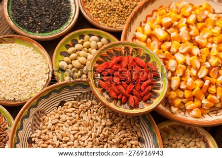 Various grain beans in small clay plates on natural textured wood background. Uncooked organic raw food. - stock photo