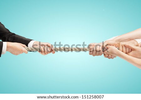 Various hands during tug war on blue backgrounds - stock photo